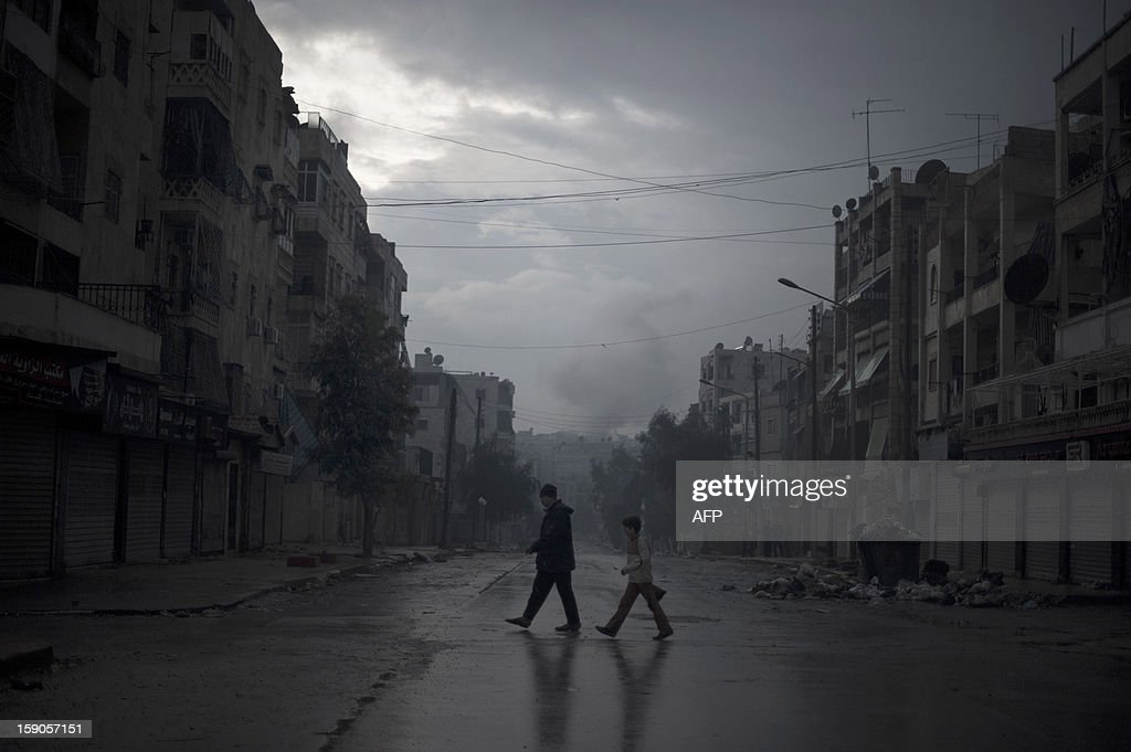 A father and son return home with vegetables, as smoke from a pro-government forces artillery strike ascends in the background, in the al-Amaria neighbourhoodin the city of Aleppo, on January 6, 2013. Syria's embattled President Bashar al-Assad in a rare televised speech denounced the opposition as 'slaves' of the West and called for a national dialogue conference to be followed by a referendum on a national charter and parliamentary elections. AFP PHOTO/ZAC BAILLIE