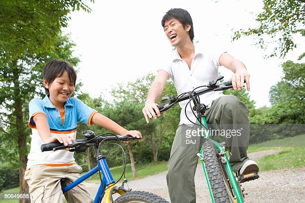 Father and son riding bicycle, smiling, summer