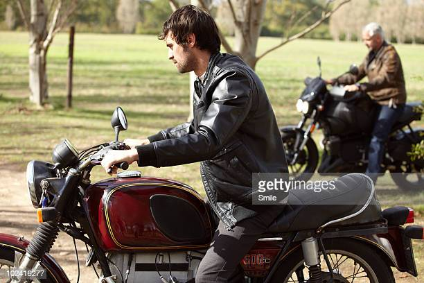 Father and son riding motorcycles in the country