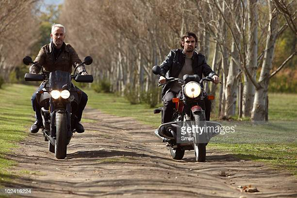 Father and son riding motorcycles on country road