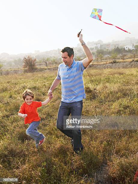 Father and son (4-6) running in field with kite, smiling