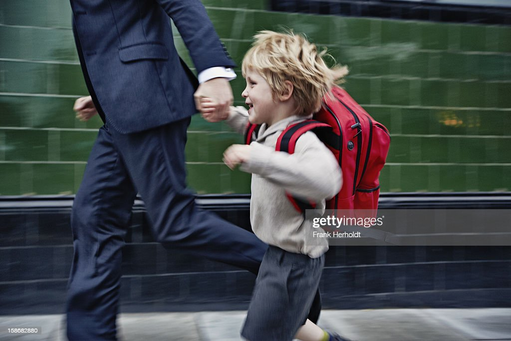 Father and son running to school : Stock Photo