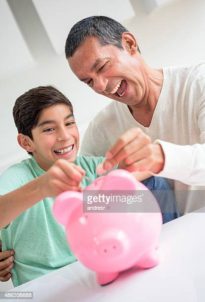 Father and son saving money in a piggybank