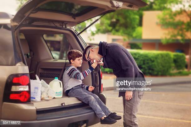 father and son sharing a doughnut after grocery shopping