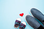Father and son shoes with red heart shape on pastel blue background. Love concept. Empty place for sentimental, lovely, cute text, quote or sayings. Flat lay.
