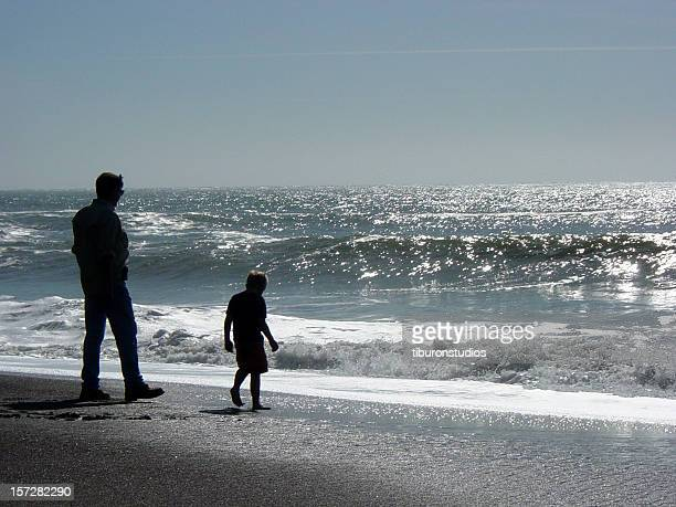 Father and Son Silhouettes by the Shore at the Beach