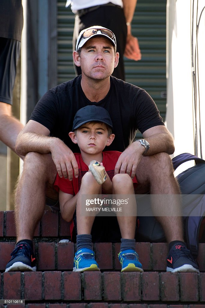 A father and son sit on the steps watching the cricket during day three of the first cricket Test match between New Zealand and Australia at the Basin Reserve in Wellington on February 14, 2016. AFP PHOTO / MARTY MELVILLE / AFP / Marty Melville
