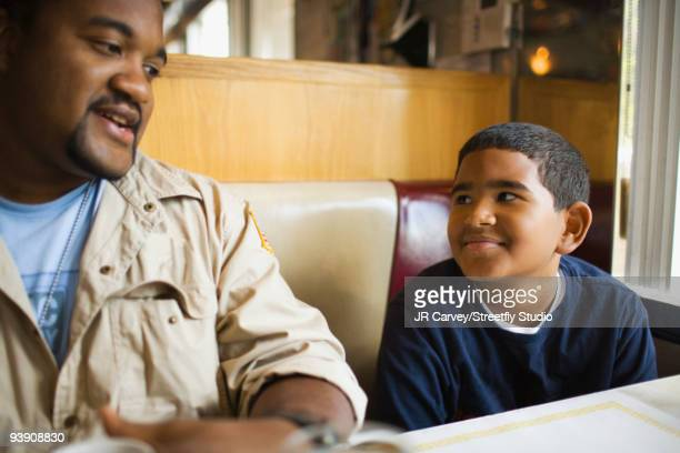 Father and son sitting at diner booth