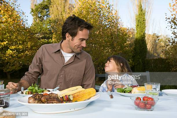 Father and son (3-4) sitting at table in garden and looking in eyes