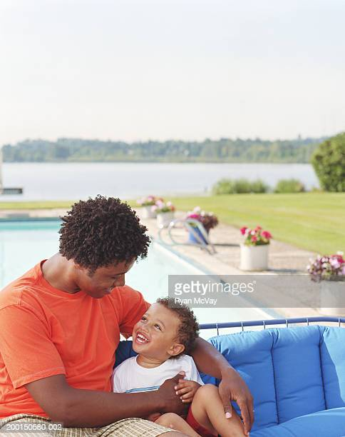 Father and son (2-4) sitting beside pool, smiling at one another