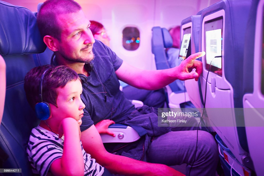 Father and son sitting in aeroplane, looking at in-flight TV screen : Stock Photo