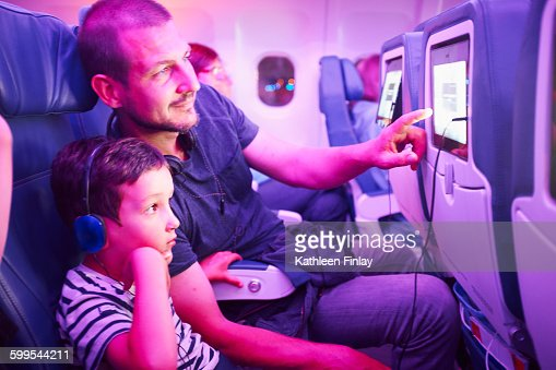 Father and son sitting in aeroplane, looking at in-flight TV screen