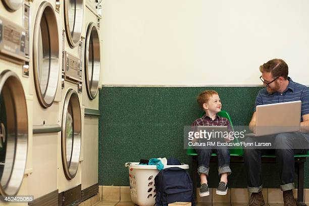 Father and son sitting in launderette using laptop and digital tablet