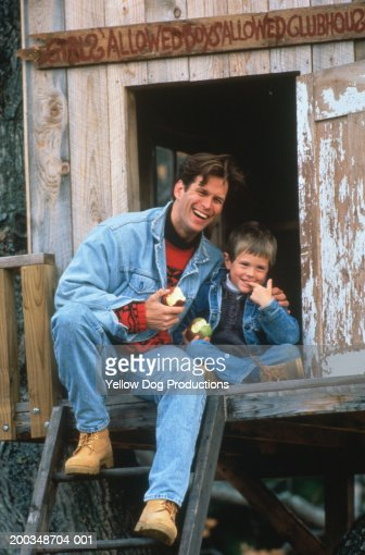 Father and son (4-6) sitting in treehouse, eating apples : Stock Photo