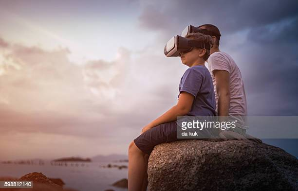 Father and son sitting in VR glasses outside at sunset
