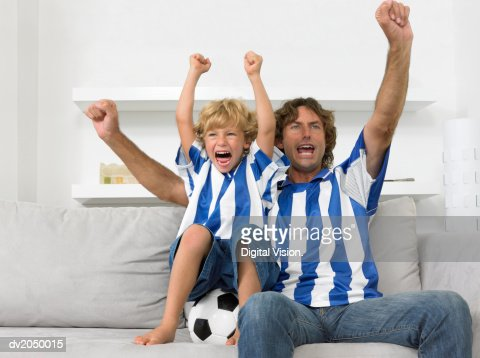 Father and Son Sitting on a Sofa, Wearing Football Strips and Cheering : Stock Photo