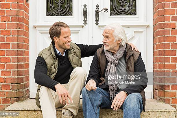 Father and son sitting on doorstep