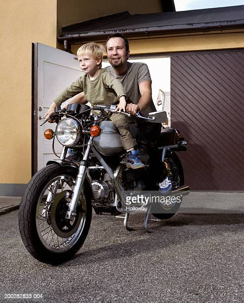 Father and son (3-5) sitting on motorbike outside garage