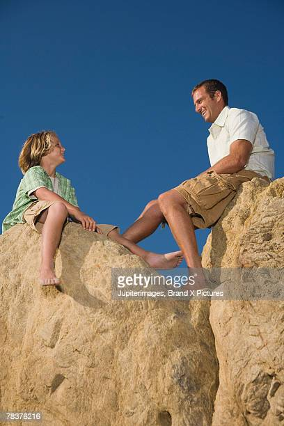 Father and son sitting on rock