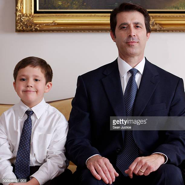 Father and son (6-7) sitting on sofa, smiling, portrait