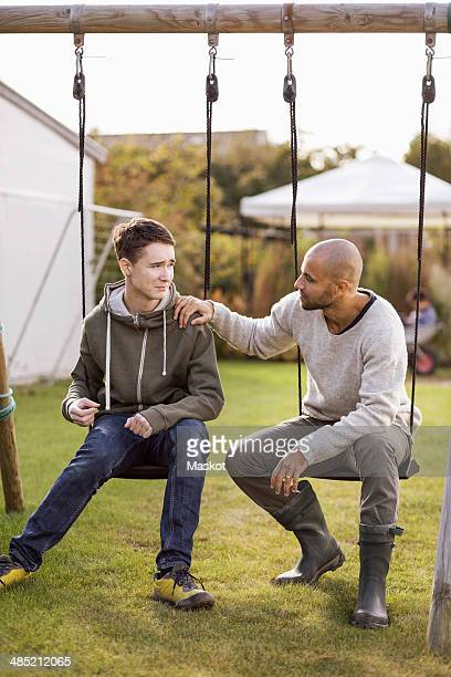 Father and son sitting on swings in garden