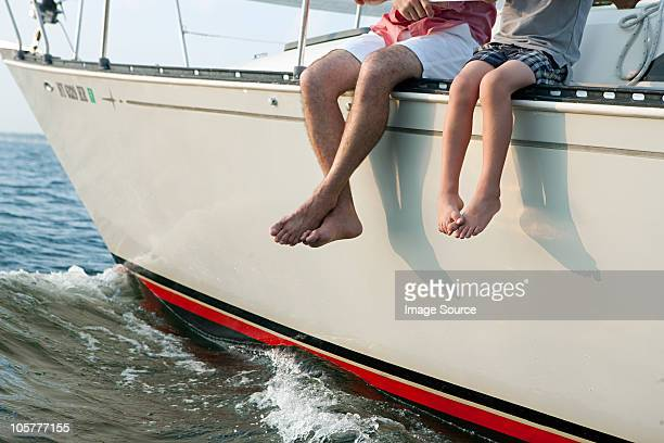 Father and son sitting on yacht, legs dangling