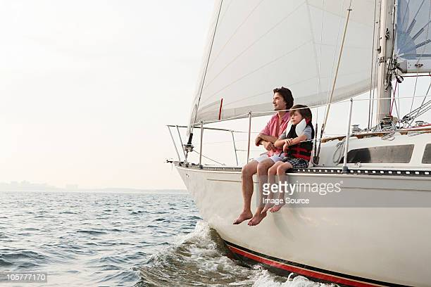 Father and son sitting on yacht