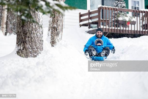 Father and Son Sledding on Snow at Christmas