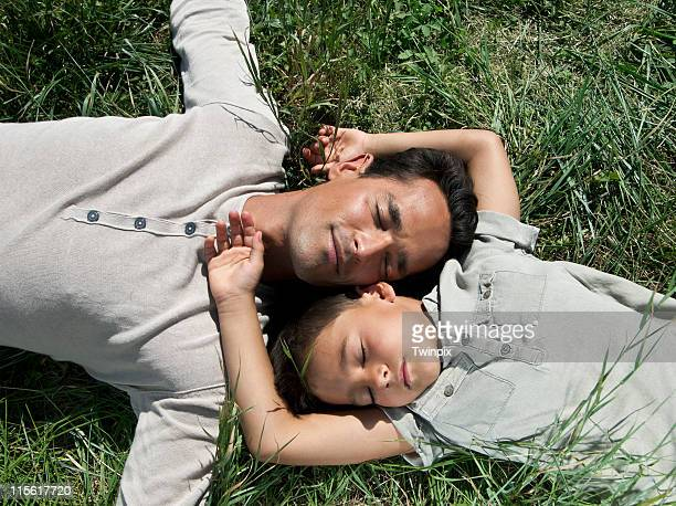 Father and son sleeping in the grass