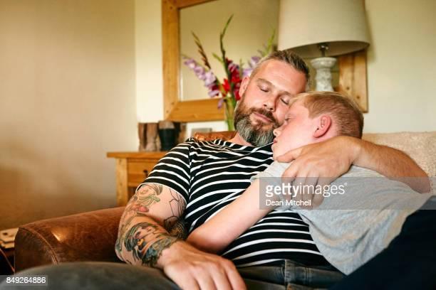 Father and son sleeping on sofa