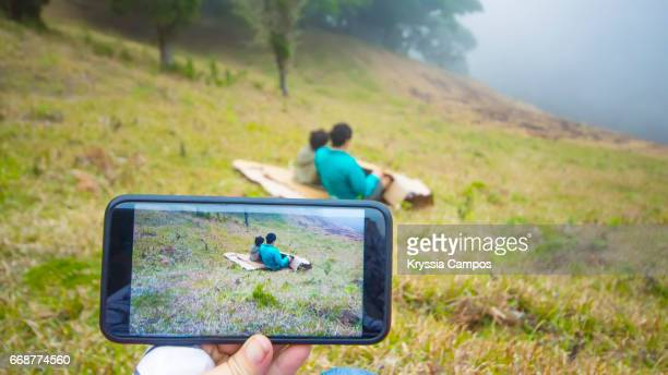 Father and Son slide down a grass hill on cardboard while are recording on video
