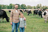father and son smiling at camera while standing near grazing cattle at farm