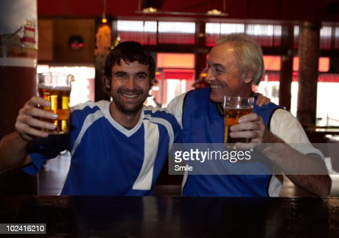 Father and son smiling in bar : Stock Photo