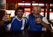 Father and son smiling in bar