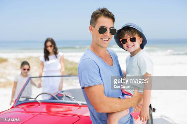 Pai e filho a sorrir perto de Carro Descapotável na praia