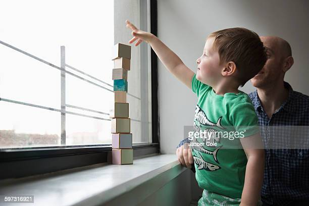 Father and son stacking blocks in window