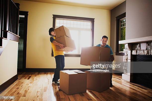 Father and son stacking boxes in house