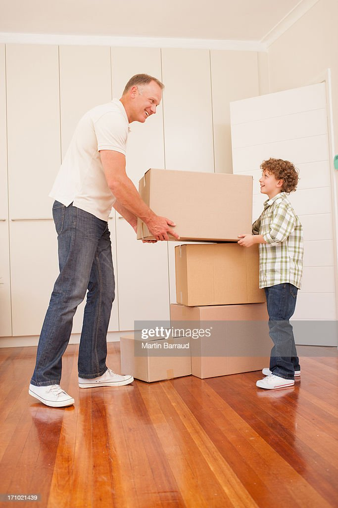Father and son stacking boxes in new house : Stock Photo
