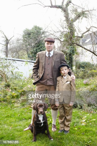 Father and son standin with their dog in garden : Stock Photo