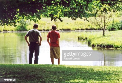 Father And Son Standing At Edge Of Pond Stock Photo Getty Images