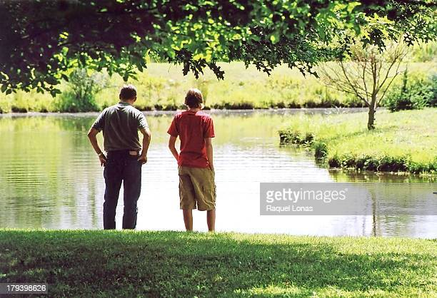 Father and son standing at edge of pond