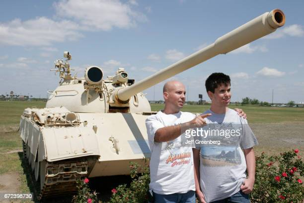 A father and son standing in front of a tank at the USS Alabama Battleship Memorial Park