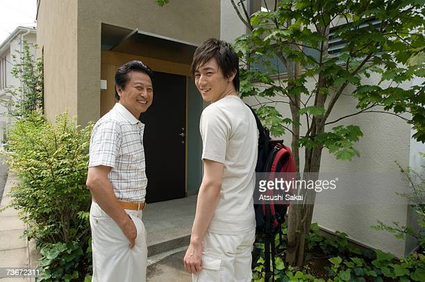 Father and son standing in front of house