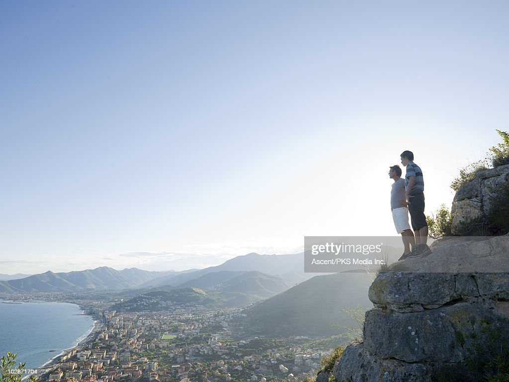 Father and son standing on cliff above town : Stock Photo