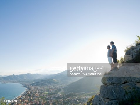 Father and son standing on cliff above town : Bildbanksbilder