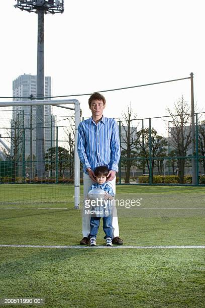 Father and son (2-4) standing on soccer field, portrait