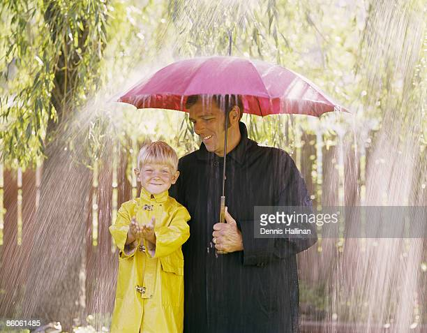Father and son standing under umbrella wearing raincoats