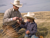 Cowboy and young son studying nature on ranch property in Big Timber, Montana