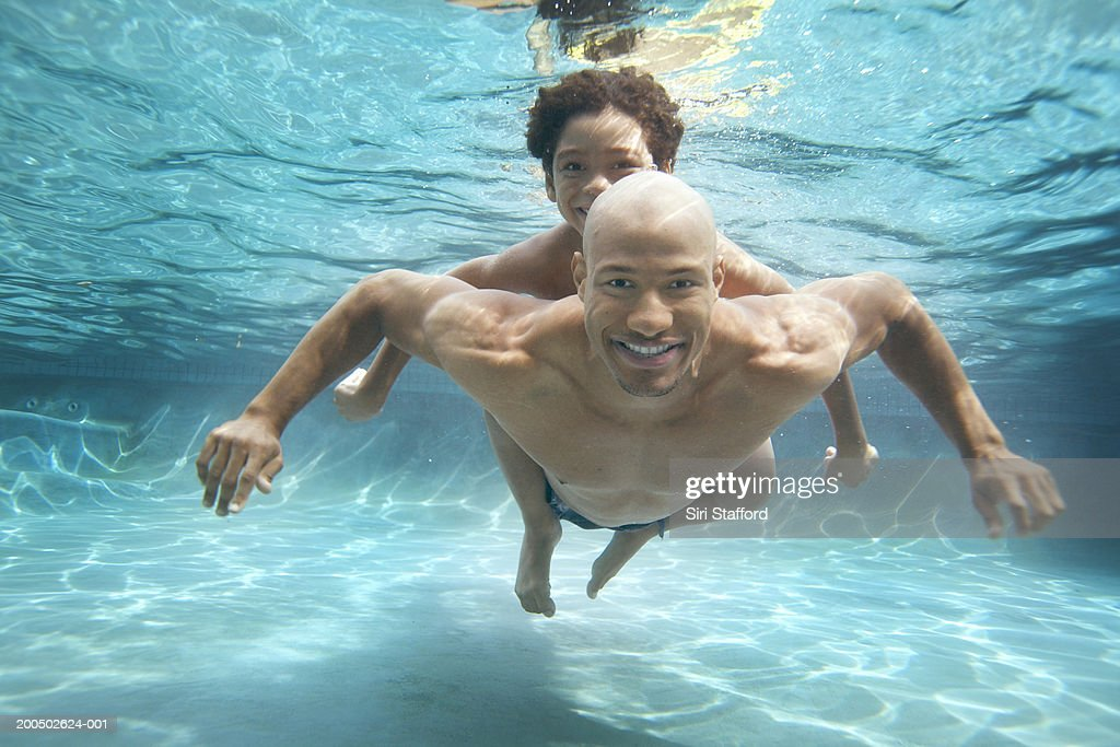 Father and son (7-9) swimming underwater : Stock Photo