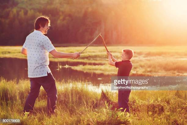 Father and son sword fight at sunset